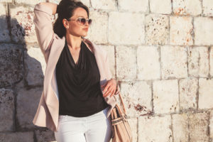Young stylish woman wearing neutral blazer, sunglasses and handbag walking on the city street in spring. Casual fashion, elegant look. Plus size model.