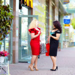 happy plus size women shopping talking on the street